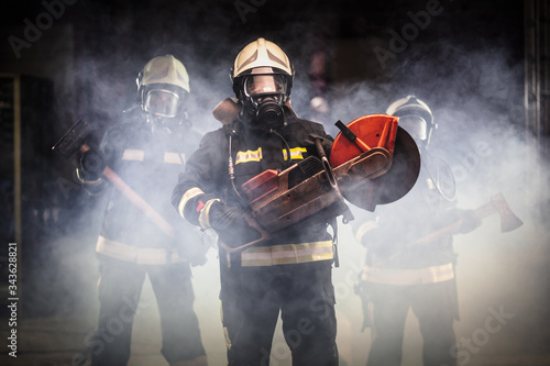 Valokuva Group of professional firefighters wearing full equipment, oxygen masks, and emergency rescue tools, circular hydraulic and gas saw, axe, and sledge hammer