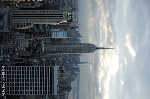 Fotografering Empire State Building With Cityscape Against Cloudy Sky