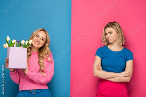 Slika na platnu Smiling girl holding bouquet near envy blonde sister on blue and pink background