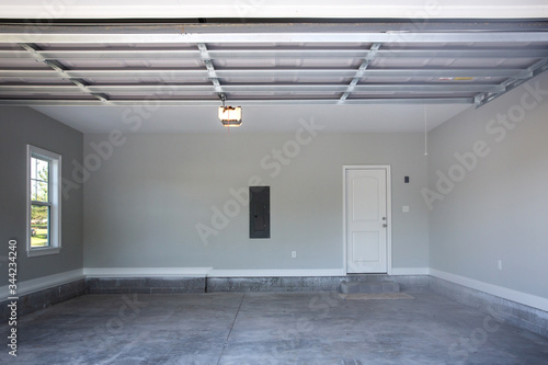 Photo Empty large two-car garage with cement floors and a door to the inside as well a