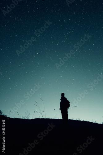 stars on the night sky and man silhouette star gazing, night landscape Fototapet