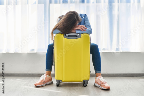 Canvas Print Woman traveler with yellow suitcase affected by flight delay and cancelled travel and vacation holiday