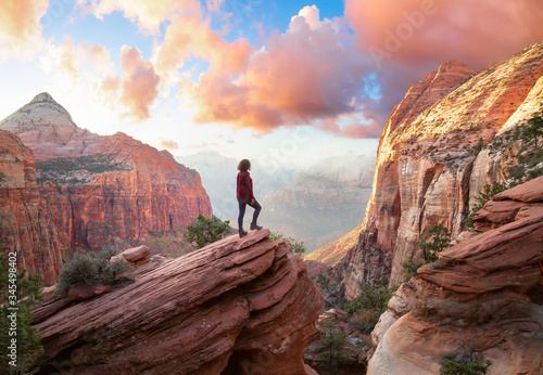 Fotografia Adventurous Woman at the edge of a cliff is looking at a beautiful landscape view in the Canyon during a vibrant sunset