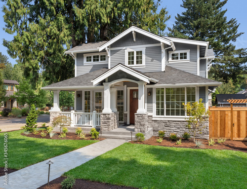 Photo New luxury home exterior with covered porch and green grass on bright sunny day