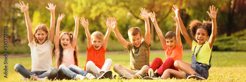 Foto Cute little children sitting on grass outdoors on sunny day