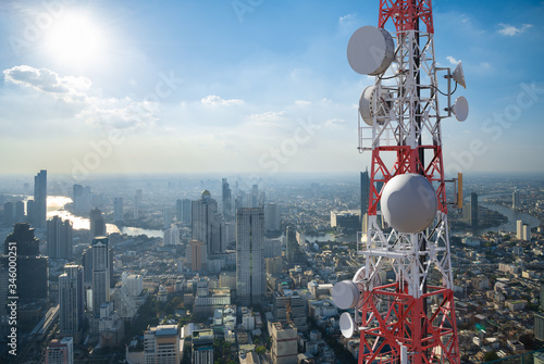 Leinwand Poster Telecommunication tower with 5G cellular network antenna on city background