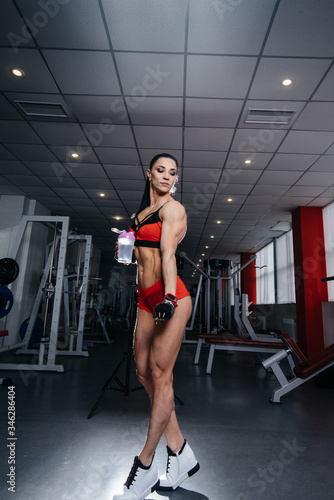 Beautiful, athletic sexy girl posing in the gym after a hard workout. Fitness, bodybuilding