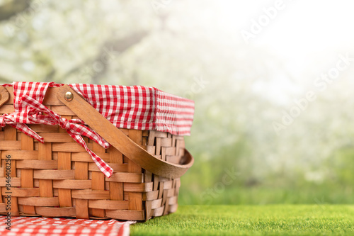 Fotografia On green grass, a picnic basket against the backdrop of the landscape