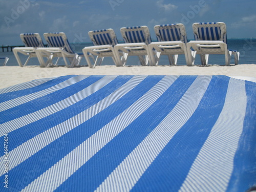 Fotografiet Close-up Of Deck Chair At Beach Against Sky