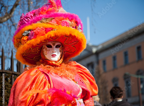 Fototapeta Portrait Of Woman In Costume And Mask During Carnival Standing Against Sky In Ci