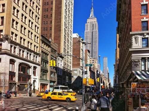 City Street By Empire State Building Against Clear Blue Sky Fototapet
