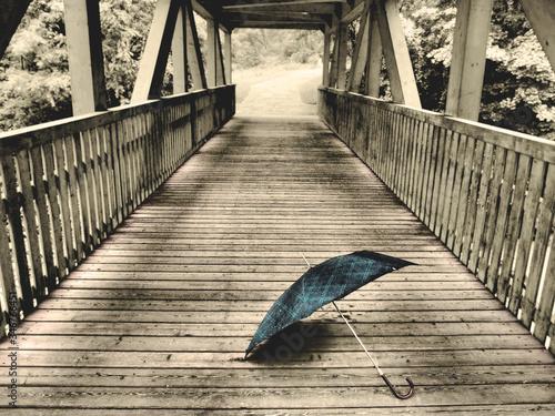 Fotografiet Open Umbrella On Wooden Footbridge