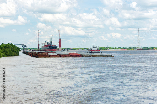 cargo carrier and barges at new orleans terminal Fotobehang