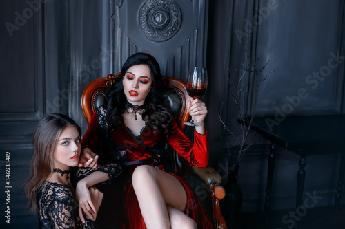 Photo Sexy gothic woman vampire evil sitting on armchair holding glass of wine blood