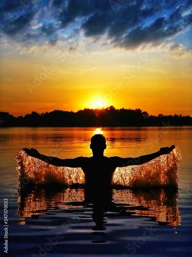 Fotografia Man Emerging From A Lake At Sunset
