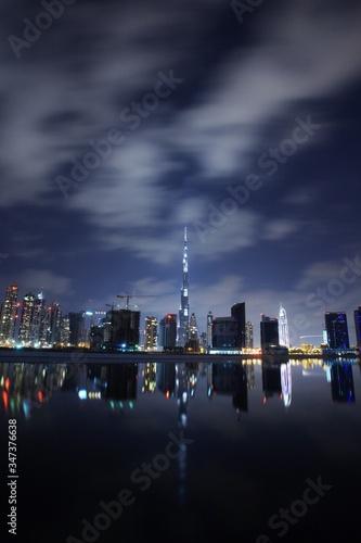 Fototapeta Burj Khalifa By Lake In Illuminated City At Night