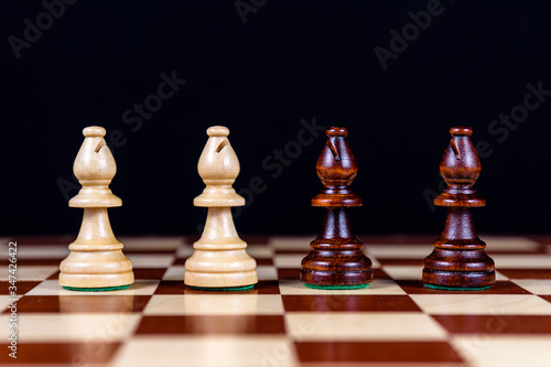Foto four chess bishops on a chessboard on a black background