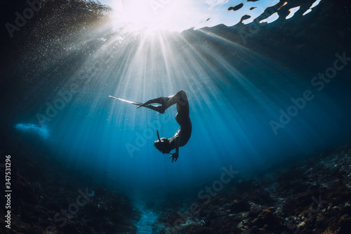 Fototapeta Free diver woman with fins glides over coral bottom and amazing sun rays