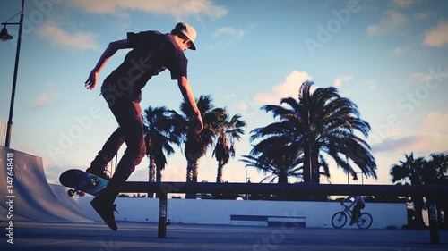 Rear View Of Man Skateboarding At Park Against Sky