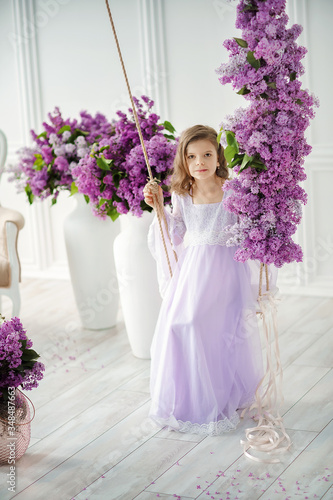 Beautiful little girl of preschool age in a delicate dress sitting on a swing decorated with flowers of lilac.