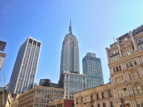 Fotografering Low Angle View Of Empire State Building With Cityscape Against Sky
