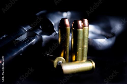 Fotografiet Close-up Of Handgun And Bullets Over Black Background