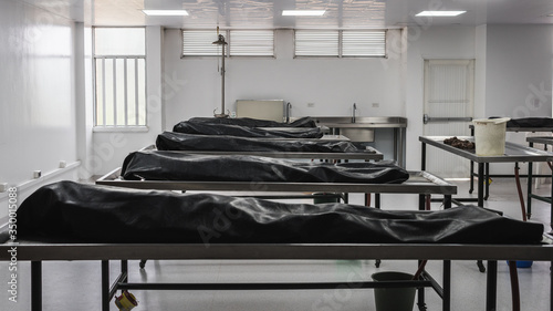 Leinwand Poster Covered human corpses on tables in a morgue / mortuary waiting for identification, autopsy, burial or cremation