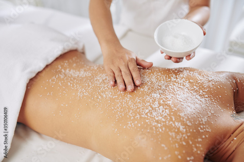 Obraz na plátně Beautician exfoliating back of young woman with salt scrub before massage