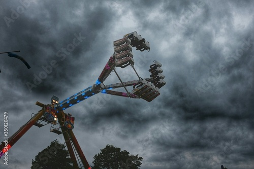 Low Angle View Of Ride At Amusement Park Against Cloudy Sky Fototapet
