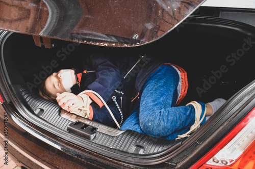 Fototapeta the captive child in the car. Illegal theft and ransom of a child