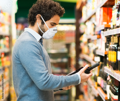 Photo Man choosing a wine bottle during coronavirus pandemic