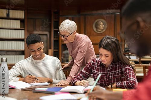 Photo Senior professor helping group of students