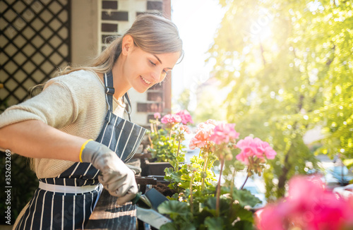 Foto Beautiful woman among flowers at her balcony during planting