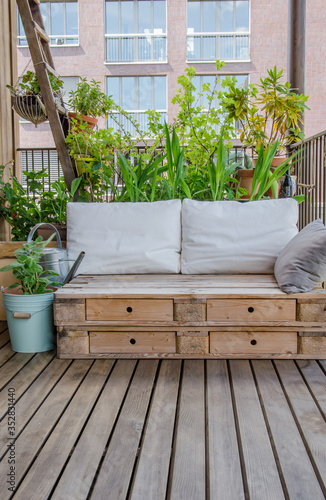 Foto Wooden pallet couch on balcony with plants in background