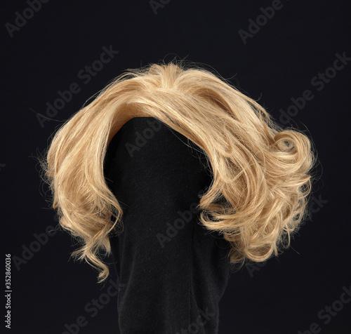 wavy blonde hair wig on black background Fototapeta