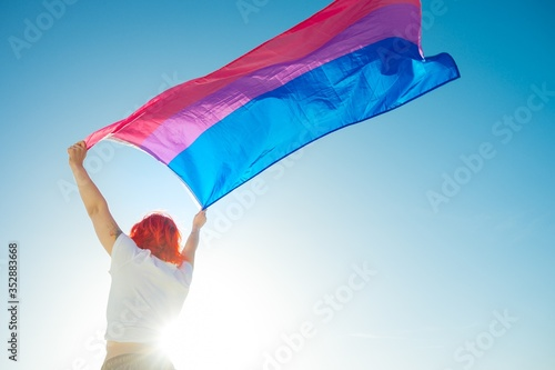 Canvas Print Beautiful low angle shot of a female waving red and blue flag