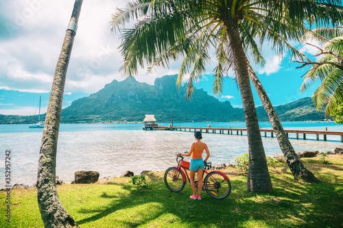 Photo Tahiti travel biking tourist on electric bicycle rental in Bora Bora island , French Polynesia eco-tourism summer vacation adventure fun cyclist girl relaxing at landscape on E-bike biking