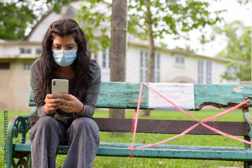 Fototapeta Young Indian woman with mask using phone while sitting with distance on park ben