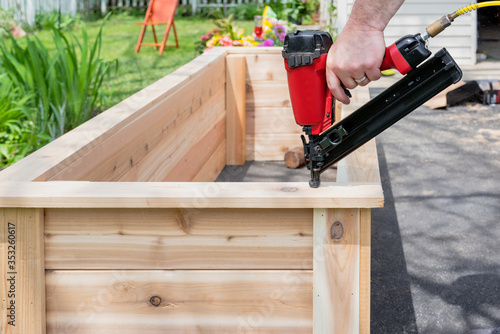 Closeup of a man using a power nail gun to build raised garden beds, with sawdust flying