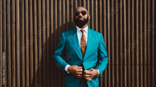 Valokuva A handsome mature bald bearded African man in a sunglasses and a fashionable blu