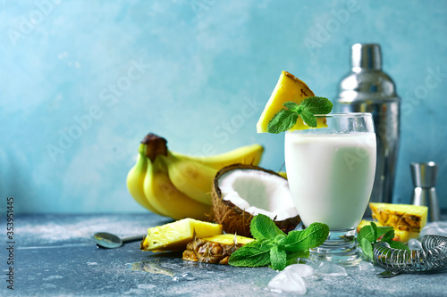 Photo Traditional caribbean cocktail pina colada with ingredients for making : cream, pineapple, coconut and milk