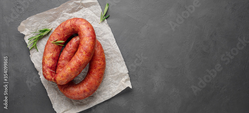 Photo Smoked sausage with rosemary on a gray slate background