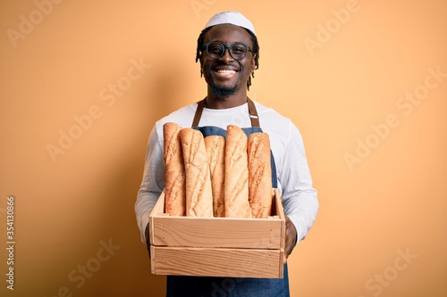 Fotografie, Obraz Young african american baker man wearing apron holding wooden box with homemade