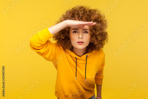 Portrait of curious curly-haired woman in urban style hoodie holding hand above eyes and peering into distance, looking far away, expecting and searching someone on horizon. studio shot isolated