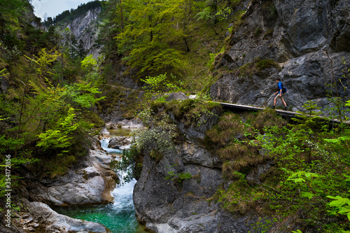Fotografiet Young Man Hiking Beneath Clear And Wild Mountain River In Green Canyon In Ötsche