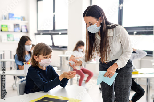 Canvas Print Teacher, children with face mask at school after covid-19 quarantine and lockdown