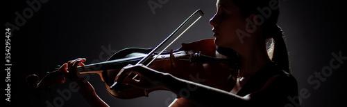 Stampa su Tela silhouette of female musician playing on violin on dark stage, panoramic orienta
