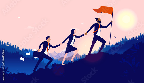 Foto Teamwork diversity - A small group of businesspeople walking up hill to plant flag at the top