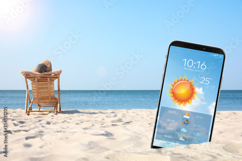 Foto Young woman relaxing in deck chair on sandy beach and smartphone with open weath
