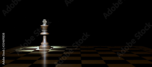 Foto king figure on a chessboard with spotlight in the dark with copy space
